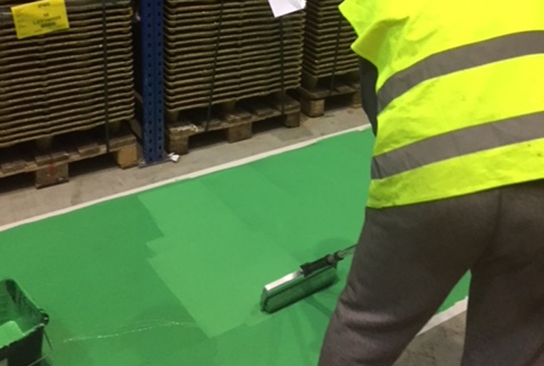 A Locus Services operative carrying out factory floor painting