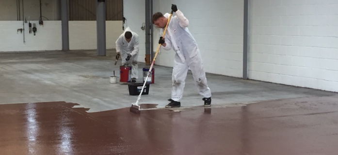 Two Locus operatives painting factory floor